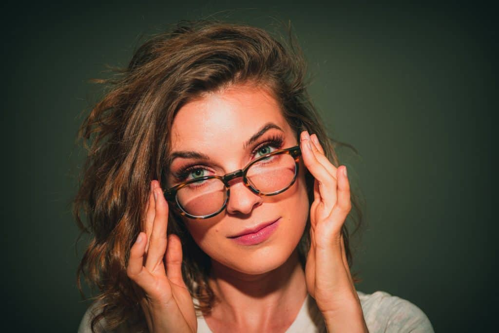attractive nerdy woman pushing her glasses up onto her face